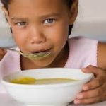 child eating soup